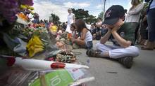 Charles Smith, 6, looks at bouquets of flowers at a memorial for seven-year-old traffic victim Georgia Walsh. Charles played on a local baseball team with Georgia. (Fred Lum/The Globe and Mail)