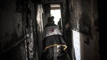 Syrian civilians, one draped in the revolutionary flag, walk through the ruins of a destroyed home in Aleppo, Syria, Thursday, Jan. 3, 2013. The area is immersed in a Syrian civil war that the United Nations estimates has killed more than 60,000 people since the revolt against President Bashar al-Assad began in March, 2011. (Andoni Lubaki/AP)