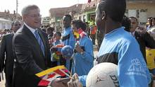 Canadian Prime Minister Stephen Harper shakes hands with a soccer player as he visits the Soacha Youth Development Centre in Soacha, Colombia, Aug. 10, 2011. (Adrian Wyld/The Canadian Press/Adrian Wyld/The Canadian Press)
