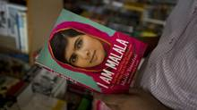 A Pakistani customer looks at a newly published book about Malala Yousafzai at a local bookshop in Islamabad on Tuesday, Oct. 8, 2013. (B.K. Bangash/Associated Press)