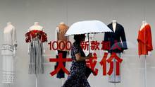 A woman carries an umbrella past a fashion outlet offering its summer sale at a shopping mall in Beijing, Monday, July 17, 2017. (Andy Wong/AP)
