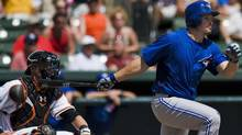 Baltimore Orioles catcher Matt Wieters (L) looks on as Toronto Blue Jays' Travis Snider (R) doubles off Baltimore starter Tommy Hunter during the second inning of a spring training baseball game in Sarasota, Florida, March 21, 2012. REUTERS/Steve Nesius (Steve Nesius/Reuters)