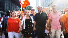 Ontario NDP Leader Andrea Horwath (left) along with NDP Leader Tom Mulcair, (right) and his wife Catherine Pinhas, (centre), attend the Labour Day Parade in Toronto on Monday, September 7, 2015. (Michelle Siu/The Canadian Press)