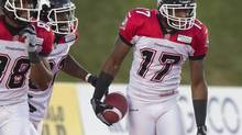 Calgary Stampeders' Maurice Price (R) celebrates with team mates after scoring a touchdown in Guelph, Ontario September 28, 2013. (FRED THORNHILL/REUTERS)