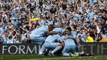 Manchester City's Pablo Zabaleta is mobbed by teammates after his goal during their English Premier League soccer match against Queens Park Rangers at the Etihad Stadium in Manchester, northern England, May 13, 2012. (Darren Staples/Reuters/Darren Staples/Reuters)