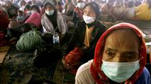 Villagers wearing face masks, who were evacuated from the area around the erupting Mount Sinabung volcano, wait at a shelter in Brastagi outside the city of Medan, North Sumatra August 29, 2010. (TARMIZY HARVA/Tarmizy Harva/Reuters)
