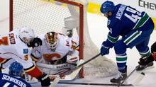 Vancouver Canucks' Darren Archibald, right, digs for the puck and eventually scores against Calgary Flames' goalie Joni Ortio, of Finland, during second period NHL hockey action in Vancouver, B.C., on Saturday March 8, 2014. (The Canadian Press)