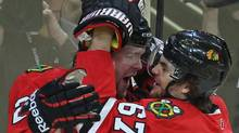 Michael Frolik #67 of the Chicago Blackhawks hugs teammate Bryan Bickell #29 after Bickells' 1st period goal against the Vancouver Canucks. (Photo by Jonathan Daniel/Getty Images) (Jonathan Daniel/2011 Getty Images)