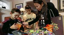 The Davidson family - Tyler, 7, Jacob, 11 and mom Sonya - separate out different Halloween treats. (Deborah Baic/Deborah Baic/The Globe and Mail)