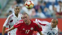 Canada's Ian Hume (17) is held as he competes for the ball against Cuba's Alain Cervantes (18) while Cuba's Silvio Pedro Minoso (4) watches from behind during Gold Cup action at Gillette Stadium in Foxboro, Mass. Monday, July 14, 2003. Cuba beat Canada, 2-0. (AP Photo/Winslow Townson) (WINSLOW TOWNSON)