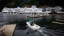 A boater heads out on the water as the B.C. Ferries vessels Queen of Oak Bay and Queen of Capilano are docked at the Horseshoe Bay Ferry Terminal in West Vancouver, B.C., on Tuesday March 5, 2013. (DARRYL DYCK For The Globe and Mail)