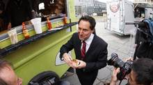 Montreal Mayor Michael Applebaum tries out a taco from a food truck on April 9, 2013, after the city gave the green light for food trucks to operate in the borough of Ville Marie this summer. (MARIO BEAUREGARD/THE CANADIAN PRESS)