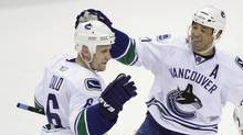 Vancouver Canucks defenceman Sami Salo (6), of Finland, is congratulated by centre Manny Malhotra, right, after scoring against the San Jose Sharks in the first period of an NHL hockey game in San Jose, Calif., Thursday, March 10, 2011. (Paul Sakuma)