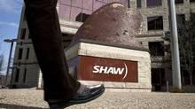 People walk past the headquarters of Shaw Communications in Calgary, Alta., (Jeff McIntosh/THE CANADIAN PRESS)