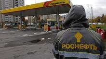 An employee in uniform stands near a Rosneft petrol station in St.Petersburg October 23, 2012. (ALEXANDER DEMIANCHUK/REUTERS)