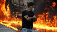A protester walks in front of a burning vehicle at Syntagma square, central Athens, Wednesday, June 29, 2011 (Petros Giannakouris/Petros Giannakouris/The Associated Press)