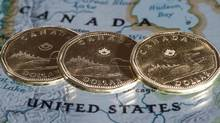 Canadian dollar coins displayed on a map of North America. (Paul Chiasson/The Canadian Press)