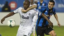 Montreal Impact's Andrés Romero, right, and Vancouver Whitecaps' Nigel Reo-Coker battle for the ball during first half first leg action of the Amway Canadian Championship final in Montreal, Wednesday, May 15, 2013. (Graham Hughes/THE CANADIAN PRESS)
