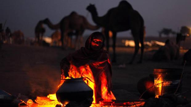 A woman prepares food early morning at the annual cattle fair in Pushkar. (Rajesh Kumar Singh/AP)