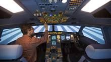 A technician operates a CAE A330-200 passenger plane flight simulator at the Lufthansa Flight Training centre in Berlin. (THOMAS PETER/REUTERS)