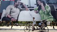 A rickshaw driver talks on his mobile phone as he rides past a billboard outside a railway station in the northern Indian city of Chandigarh. (AJAY VERMA/REUTERS)