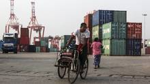 A man rides a rickshaw pasts stacked containers as cranes stand in the background at the Myanmar Industrial Port in Rangoon, Myanmar, on Tuesday, Oct. 14, 2014 in a file photo. (Dario Pignatelli/Bloomberg)