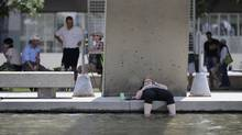 The waters of the reflecting pool at Nathan Phillip Square offers a cooling break for this woman as she soaks her feet in the water during a lunch break on June 20 2012. Hot, humid weather smotheredTorontoand southern Ontario for another day with humidex readings into the 40's. (Fred Lum/The Globe and Mail)