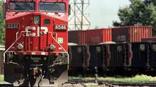 A Canadian Pacific locomotive sits parked as another hauls rail cars through the main CP yard in Calgary in this file photo. (Jeff McIntosh/The Canadian Press)