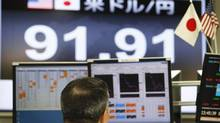 A video board shows the value of the Japanese yen against the U.S. dollar as a currency trader works at a foreign exchange company in Tokyo, Feb. 26, 2013. (Koji Sasahara/AP)