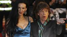 Mick Jagger of the The Rolling Stones, right, poses for photographers with his partner former U.S. model L'Wren Scott as they arrive for the UK premiere of the film 'Shine A Light' at the Odeon cinema in Leicester Square, London, Wednesday April 2, 2008 (MATT DUNHAM/AP)