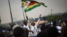 A supporter of the Zimbabwean opposition party Zimbabwe People First waves a flag ahead of an address by the party's leader in Mamelodi on Sept. 17, 2016. (JOHN WESSELS/AFP/Getty Images)