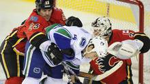 Calgary Flames' Scott Hannan (L) pushes Vancouver Canucks' Aaron Volpatti (C) out from in front of Flames' goalie Miikka Kiprusoff during the second period of their NHL hockey game in Calgary, Alberta, November 1, 2011. REUTERS/Todd Korol (Todd Korol/Reuters)
