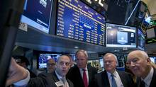 Goldman Sachs specialist trader Meric Greenbaum (L) shows executives from Marine Harvest; Chairman Ole Eirik Leroy, (C) John Fredriksen (2nd R) and Lief Rode Onarheim (R) the price of their company's stock before it begins trading on the floor of the New York Stock Exchange January 28, 2014. (BRENDAN MCDERMID/REUTERS)