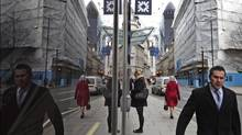 Reflected in a window, people walk in London's City financial district, Tuesday, Feb. 14, 2012. (Lefteris Pitarakis/AP)