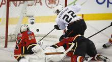 Anaheim Ducks' Mathieu Perreault, right, scores as Calgary Flames goalie Karri Ramo, left, from Finland, and Ladislav Smid, from the Czech Republic, look on during third period NHL hockey action in Calgary, Alta., Wednesday, March 26, 2014. (Jeff McIntosh/THE CANADIAN PRESS)