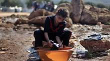 A Syrian girl who fled with her family from the violence in their village, washes clothes at a displaced camp, in the Syrian village of Atma, near the Turkish border with Syria, Nov. 5, 2012. (Khalil Hamra/AP)