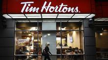 A pedestrian walking past the Tim Hortons coffee shop in Toronto on Nov. 8, 2016. Tensions are heating up between Tim Hortons Inc. and its franchisees as a battle over the fast-food chain's order-and-pay mobile app is delaying its launch. (Fred Lum/The Globe and Mail)