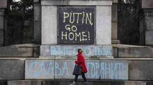 "A woman walks past a Bulgarian communist-era monument painted by unknown people in Sofia March 5, 2014. The monument was painted overnight in Ukrainian and Polish national flag colours together with texts reading ""Katyn 5.03.1940"", ""Crimea 2014"" and ""Putin go home!"" as what appears to be an artistic condemnation of the Russian stance towards Ukraine. Also a reminiscence of the Katyn massacre where on March 5, 1940 thousands of Polish officers, taken as war prisoners, were killed by the Soviet secret police. REUTERS/Stoyan Nenov (BULGARIA - Tags: POLITICS CIVIL UNREST) (STOYAN NENOV/REUTERS)"