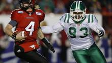 Calgary Stampeders' quarterback Drew Tate (L) rolls away from Saskatchewan Roughriders' Tearrius George during the second half of their West Division semi-final CFL football game in Calgary, Alberta, November 11, 2012. (TODD KOROL/REUTERS)