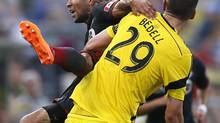 Toronto FC defender Justin Morrow, rear, falls to the ground after going for a header against Columbus Crew forward Adam Bedell (29) in the first half of an MLS soccer game on Aug. 9 in Columbus, Ohio. (Eamon Queeney/AP)