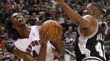 Toronto Raptors Chris Bosh battles for the ball with San Antonio Spurs Theo Ratliff (R) during the first half of their NBA basketball game in Toronto, January 3, 2010. REUTERS/Mark Blinch (MARK BLINCH)
