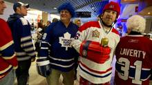 "Brothers, David Groen, the Leafs fan in blue wig, left, and Gerry Groen, the Habs fan in the ""helmet,"" making laps of the concourse at the ACC before the first period of the Toronto Maple Leafs versus the Montreal Canadians at the ACC on Toronto on April 27, 2013. (Peter Power/The Globe and Mail)"