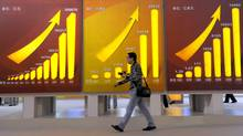 A visitor to Beijing walks past billbards showing China's rising economic indicators at an exhibition showcasing China's achievements over the last six decades on Sept. 22, 2009 (LIU JIN)