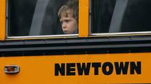 A child looks out of the window of a school bus carrying students from the Newtown school district as it makes its way past the funeral for one of the Sandy Hook student victims, on Dec. 18, 2012. (SHANNON STAPLETON/Reuters)