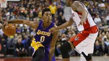 Los Angeles Lakers forward-guard Nick Young (0) tries to carry the ball past Toronto Raptors guard Julyan Stone (77) defends at the Air Canada Centre. Los Angeles defeated Toronto 112-106. (John E. Sokolowski/USA Today Sports)
