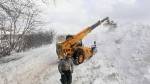 Workmen clear a snow drift blocking the Cushendall Road in Northern Ireland as wintry weather continues to cause havoc across the United Kingdom, March 24, 2013. (CATHAL MCNAUGHTON/Reuters)