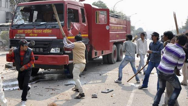 Protesters damage a fire engine during a strike in Noida, on the outskirts of New Delhi, Feb. 20, 2013. Sporadic violence has broken out in India at the beginning of a two-day strike by labour unions protesting rising prices and government economic policies. (STRINGER/INDIA/REUTERS)