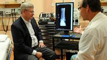 Prime Minister Stephen Harper speaks with a physician at Yellowknife's Stanton Hospital on Aug. 25, 2011. (Sean Kilpatrick/THE CANADIAN PRESS)