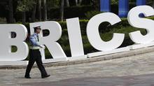 A traffic policeman walks past a signage decoration for BRICS Summit outside the Sheraton Hotel, the venue of BRICS (Brazil, Russia, India, China and South Africa) Summit in Sanya, China's Hainan province, April 13, 2011. (JASON LEE/Jason Lee/Reuters)