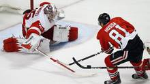 Detroit Red Wings' Jimmy Howard (L) pokes the puck away from Chicago Blackhawks' Marian Hossa during the first period of their NHL hockey game in Chicago, Illinois, April 12, 2013. (JIM YOUNG/REUTERS)